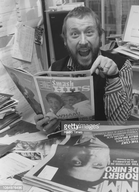 Portrait of BBC Radio producer John Walters reading a copy of Smash Hits magazine photographed for Radio Times in connection with the John Peel Show...