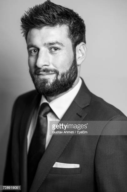 portrait of bearded businessman against gray background - waist up stock pictures, royalty-free photos & images