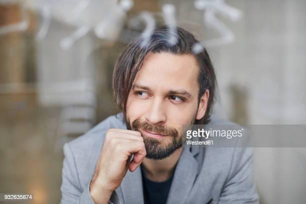Portrait of bearded businessman looking out of window