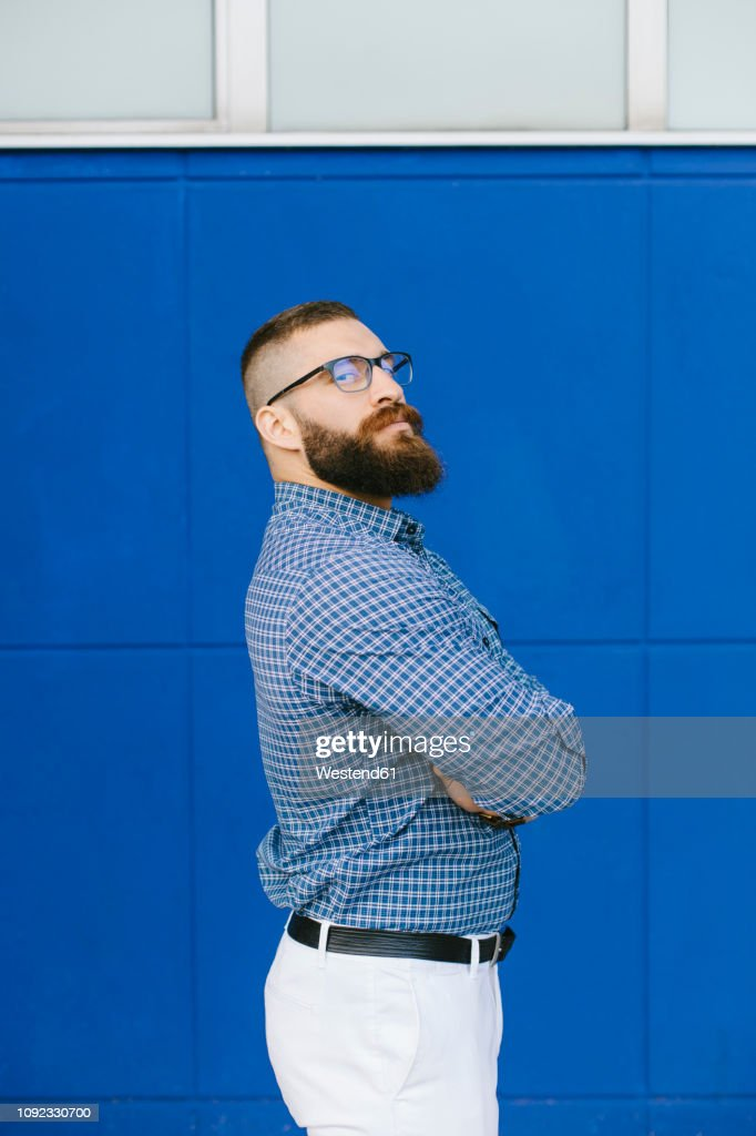 Portrait of bearded hipster businessman wearing plaid shirt standing in front of blue background : Stock Photo