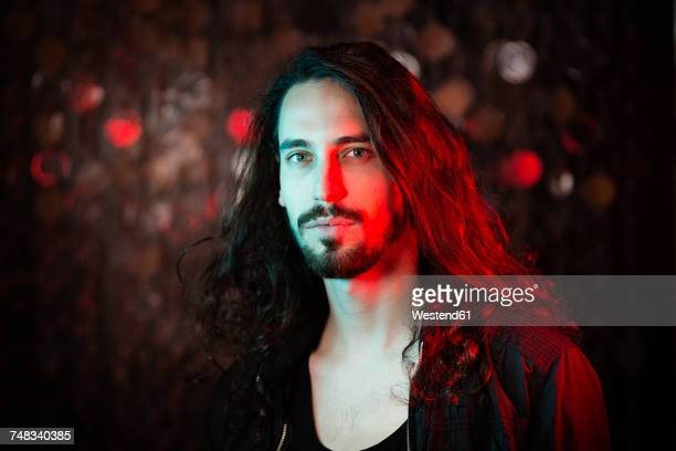 portrait of bearded long-haired young man in red light - cabello largo fotografías e imágenes de stock