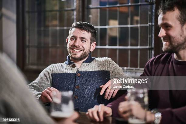 Portrait of bearded male sat smiling with his friends at a table of a pub with his friends