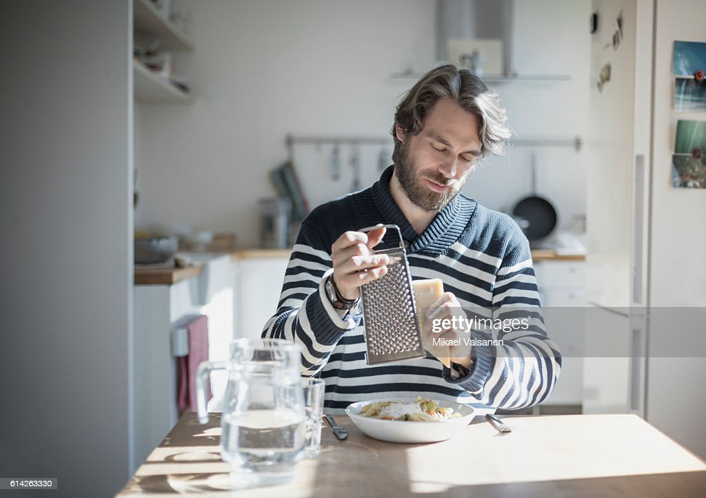 Portrait of bearded man eating at home : Stock Photo