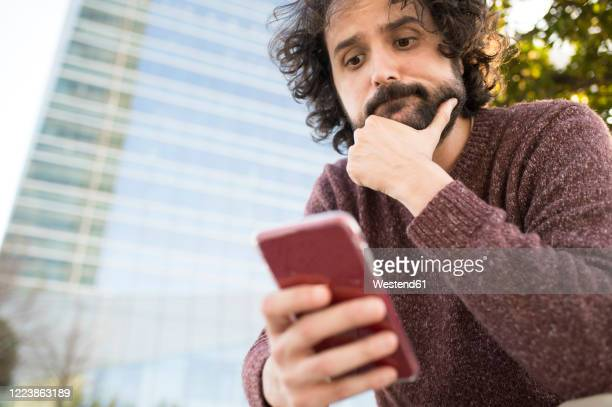 portrait of bearded man looking at smartphone outdoors - uncertainty stock pictures, royalty-free photos & images