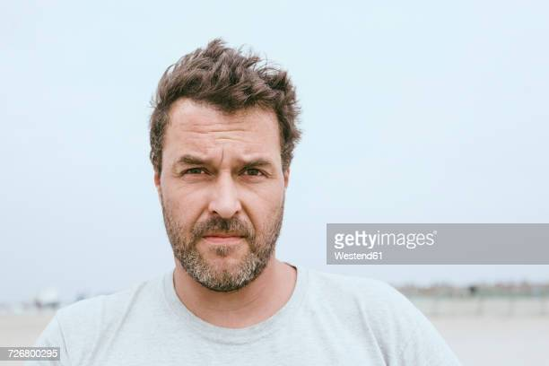 portrait of bearded man on the beach - serious stock pictures, royalty-free photos & images