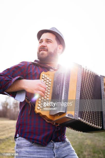 portrait of bearded man playing accordion on a meadow at backlight - accordionist stock pictures, royalty-free photos & images