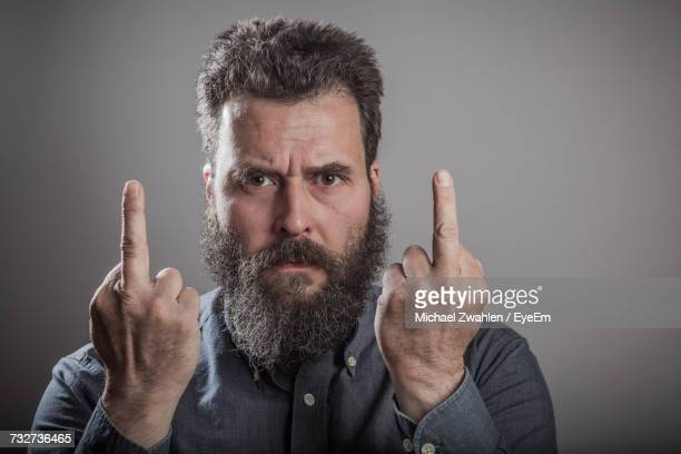 Portrait Of Bearded Man Showing Middle Fingers Against Gray Background