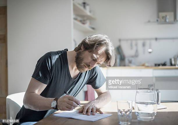 portrait of bearded man sitting at home - form filling stock pictures, royalty-free photos & images