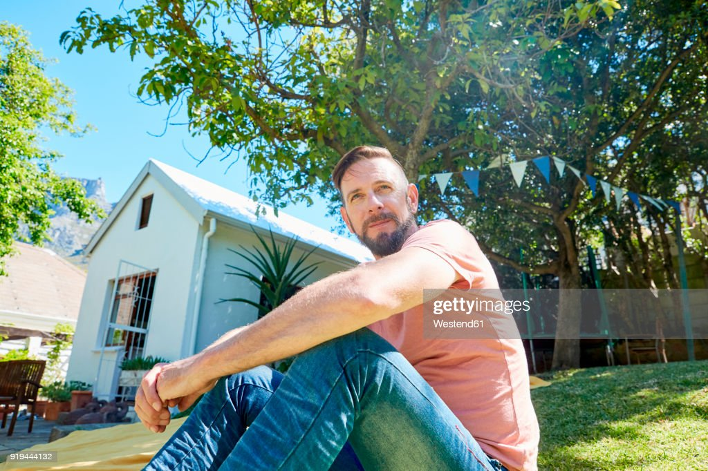 Portrait of bearded man sitting in front of a house : Stock Photo