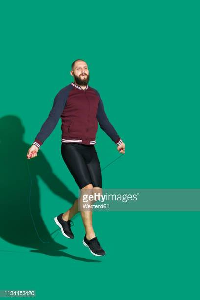 portrait of bearded man skipping rope in front of green backgrpund - green shorts stock photos and pictures