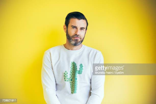 Portrait Of Bearded Man Standing Against Yellow Background