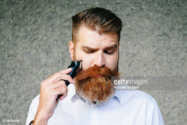 portrait of bearded man trimming his beard - beard stock pictures, royalty-free photos & images