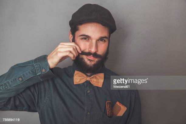 portrait of bearded man wearing cap, denim shirt, cork bow tie, wearing wooden combs for beard and mustache in his pocket - mustache stock pictures, royalty-free photos & images