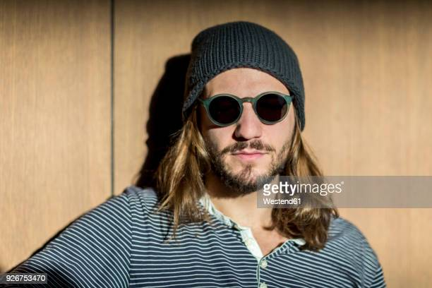 portrait of bearded man with long hair wearing sunglasses and wooly hat - mütze stock-fotos und bilder