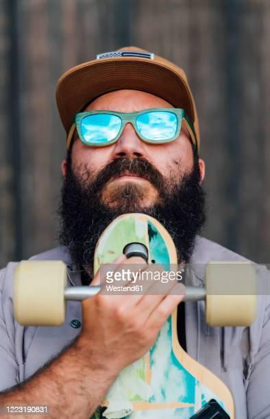 portrait of bearded man with skateboard wearing mirrored sunglasses - só um homem maduro imagens e fotografias de stock