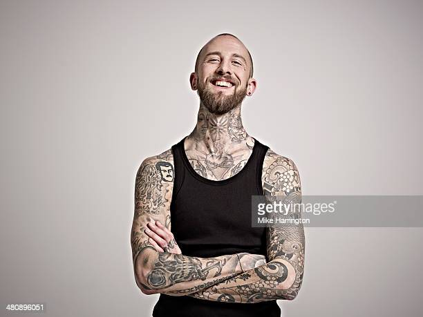 Portrait of bearded man with tattoos laughing.