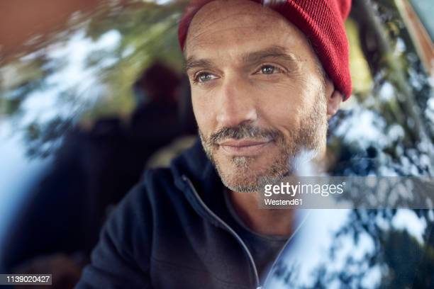 portrait of bearded mature man behind windscreen - berufsfahrer stock-fotos und bilder