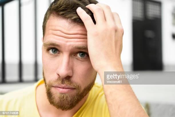 portrait of bearded young man - mão no cabelo - fotografias e filmes do acervo