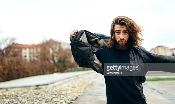 portrait of bearded young man putting on his leather jacket - black jacket stock pictures, royalty-free photos & images