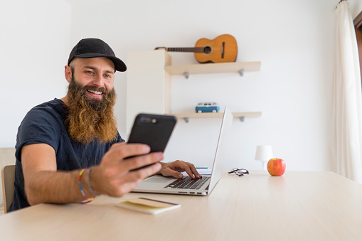 Portrait of bearded young man sitting at desk with laptop looking at cell phone - gettyimageskorea