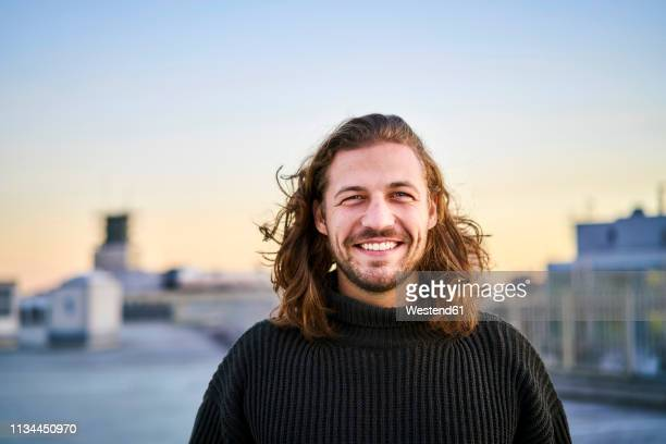 portrait of bearded young man smiling - long hair stock pictures, royalty-free photos & images