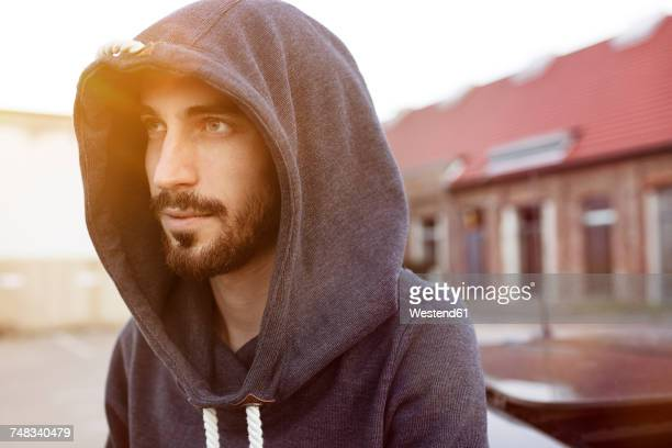 portrait of bearded young man wearing hooded jacket - capucha fotografías e imágenes de stock