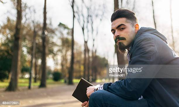 Portrait of bearded young man with book in the park