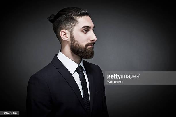 Portrait of bearded young man with bun wearing black jacket and tie in front of grey background