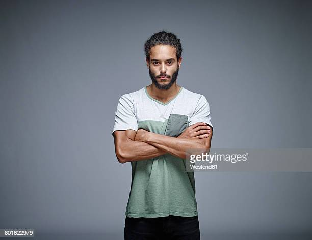 portrait of bearded young man with crossed arms in front of grey background - dismissal stock photos and pictures