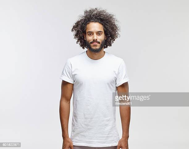 portrait of bearded young man with curly brown hair wearing white t-shirt - bovenlichaam stockfoto's en -beelden