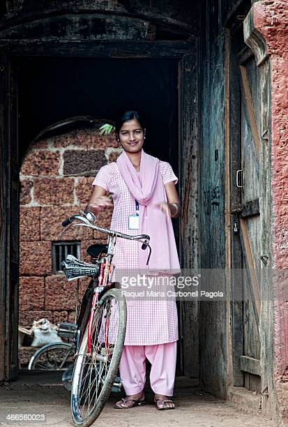 Portrait of beautiful and smiling Indian young girl with bicycle