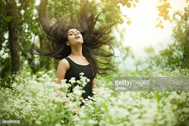 portrait of beautiful asian girl in meadow doing hair toss. - beautiful east indian women stock pictures, royalty-free photos & images