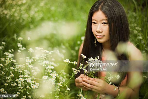 Portrait de fille magnifique d'origine asiatique dans Prairie tenant des fleurs sauvages.
