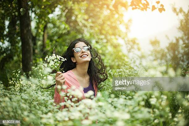 portrait of beautiful asian girl in meadow holding wild flowers. - indian beautiful girls stock photos and pictures