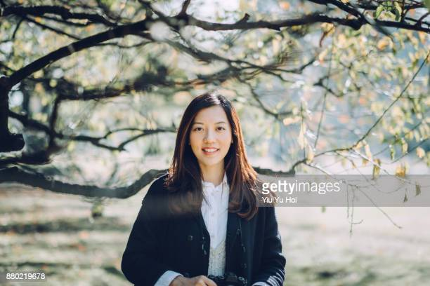 Portrait of beautiful Asian woman holding camera enjoying the sunlight and scenics in nature
