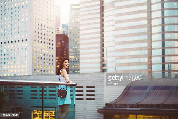 Portrait of beautiful Asian woman standing against the iconic cityscape of Hong Kong while looking up to the sky during sunset.