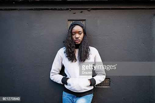 Portrait of beautiful black woman in jeans and jumper against black wall