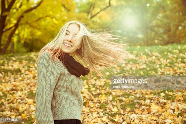 Retrato de niña rubia hermosa en otoño con resplandor solar.