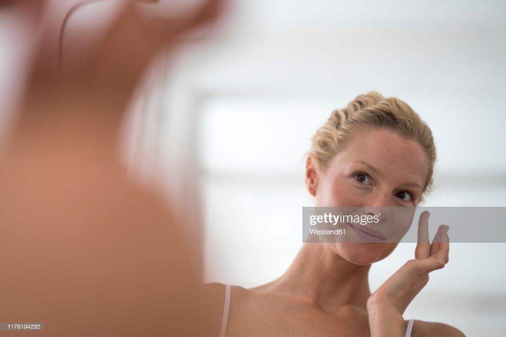 Portrait of beautiful blond woman applying eye cream : Stockfoto