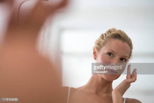 portrait of beautiful blond woman applying eye cream - lichaamsverzorging en schoonheid stockfoto's en -beelden