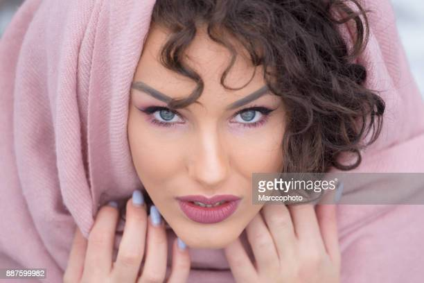 Portrait of beautiful blue eye curly hair girl with one half of face covered with scarf outdoor on winter day