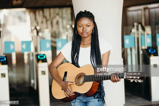 portrait of beautiful braided young street performer holding her guitar - songwriter stock pictures, royalty-free photos & images
