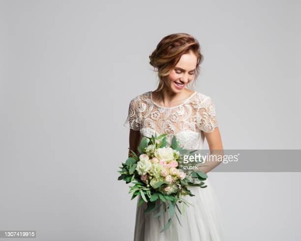 portrait of beautiful bride holding flowers - embellished dress stock pictures, royalty-free photos & images