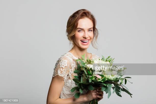 porträt der schönen braut hält blumen - izusek stock-fotos und bilder