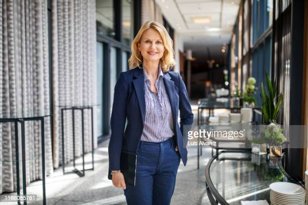 portrait of beautiful businesswoman in auditorium corridor - three quarter length stock pictures, royalty-free photos & images