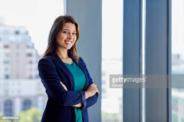 Portrait of beautiful businesswoman standing in creative office. Smiling executive is with arms crossed against window. She is in smart casuals.