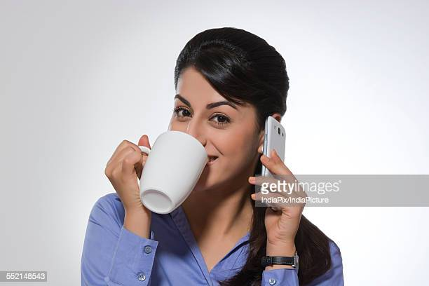 Portrait of beautiful businesswoman using phone while having coffee against gray background