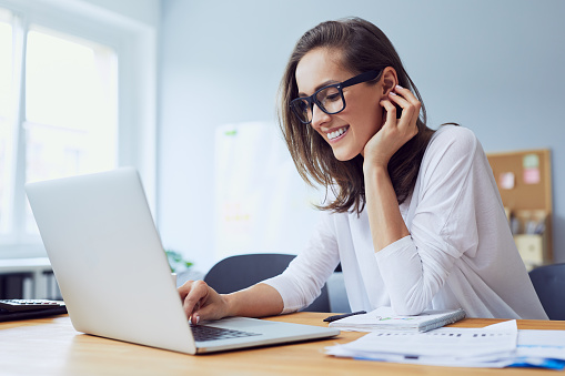 Portrait of beautiful cheerful young businesswoman working on laptop and laughing in home office 1031398222