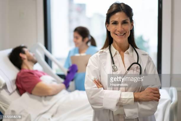 verticale de beau docteur féminin confiant souriant à l'appareil-photo tandis que le patient se trouve sur le lit d'hôpital parlant à l'infirmière - down blouse photos et images de collection