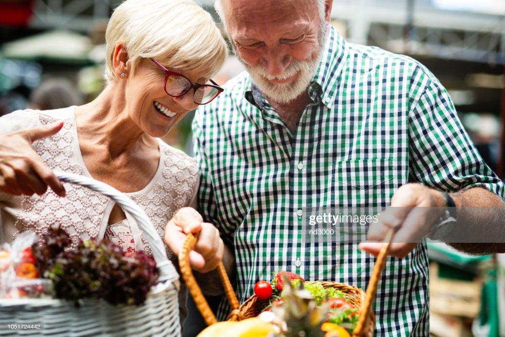 Portrait of beautiful elderly couple in market buing food : Stock Photo